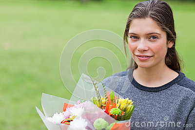 Young calm girl holding a bunch of flowers