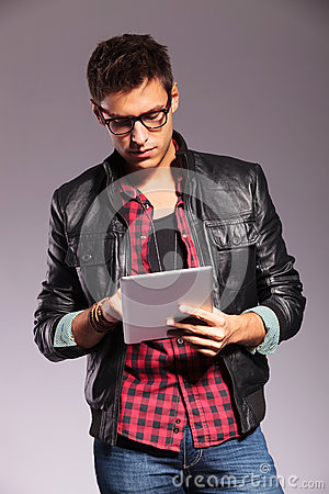Young casual man with glasses working on tablet