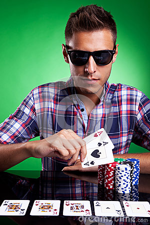Young casual man and his strong poker hand