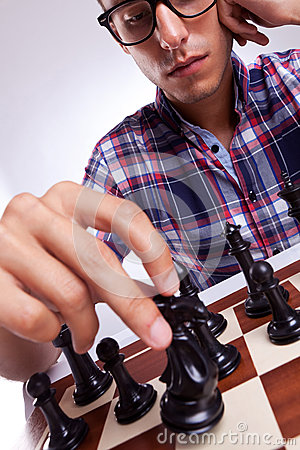 Young casual man moving his chess piece