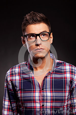 Young casual man wearing glasses and looking up
