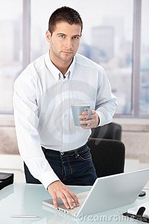 Young casual office worker using laptop in office