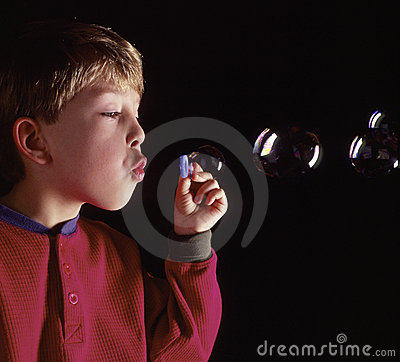 Young caucasian boy blowing bubbles