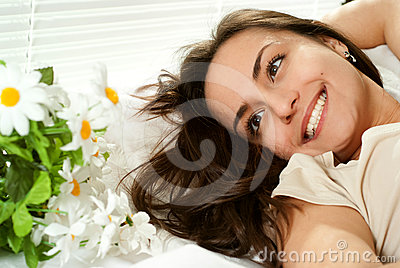 Young Caucasian girl lying in bed with flowers