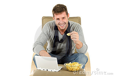 Young caucasian man, chips and netbook
