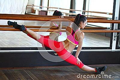 Young caucasian woman dancer near the mirror