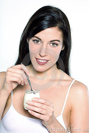 Young caucasian woman portrait  eating yogurt