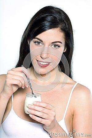 Young caucasian woman portrait  eating yogurt