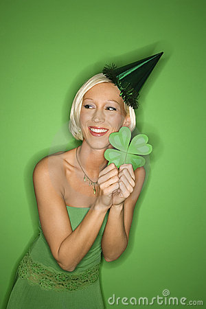 Young Caucasian woman wearing party hat and holding shamrock.