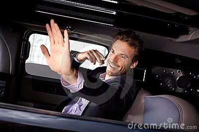 Young celebrity waving from limousine smiling