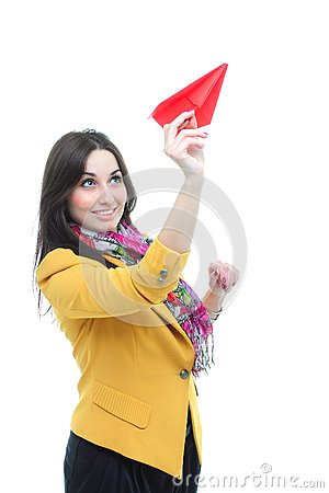Young charming brunette launching a paper airplan