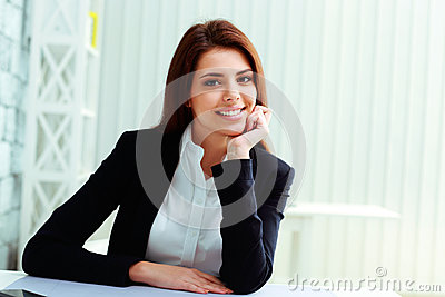 Young cheerful businesswoman sitting at the table on her workplace