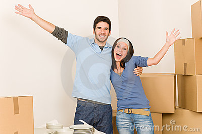 Young cheerful couple moving into new home