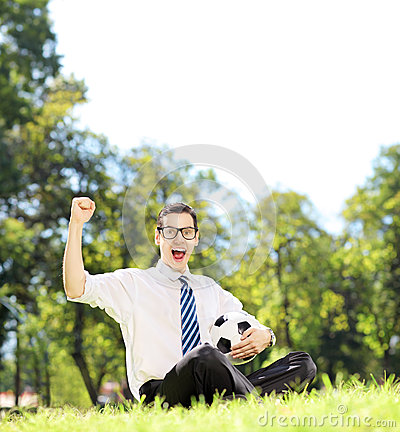 Young cheerful man holding a ball and gesturing happiness in the