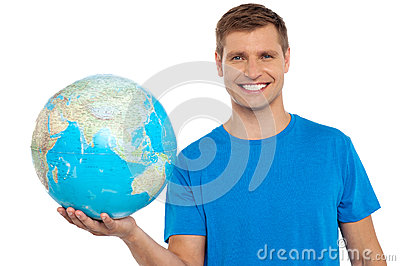 Young cheerful man holding a globe in his hand