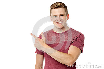 Young cheerful man pointing away