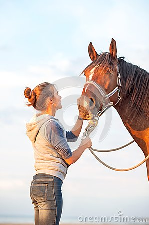 Free Young Cheerful Teenage Girl Stroking Brown Horse`s Nose. Outdoor Royalty Free Stock Photography - 106409287
