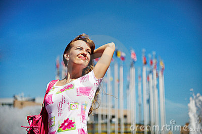 Young cheerful woman on background of sky