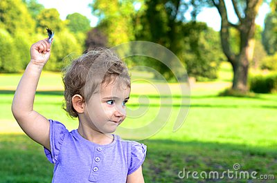 Young child, girl, toddler, holding a feather high as she plays in the park.
