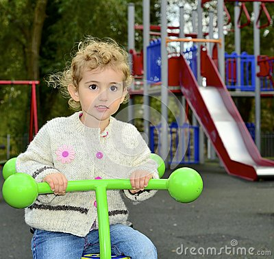 Young child outdoors having fun on a see-saw.