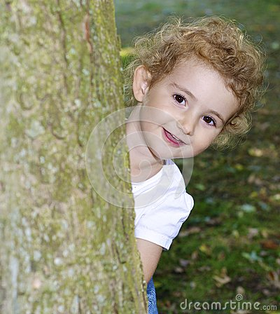 Young child playing hide and seek in the park, hiding behind a tree. Very pretty.