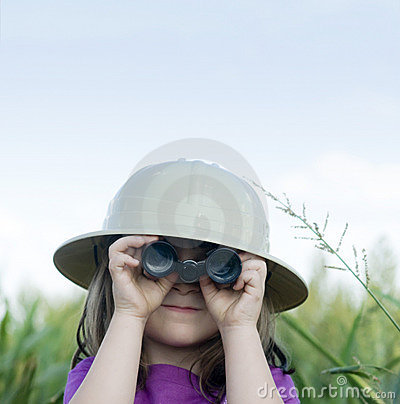 Young child searching with safari hat and binocula