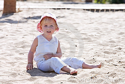 Young child sitting on beach with pink hat