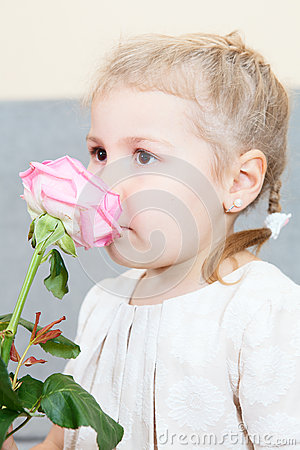 Young child smelling a pink rose