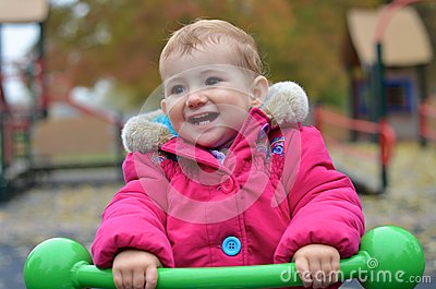 Young child, smiling, playing on a see-saw at the
