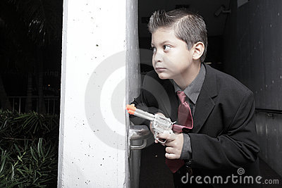 Young child in a suit with a gun