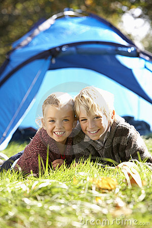 Young children pose outside of tent