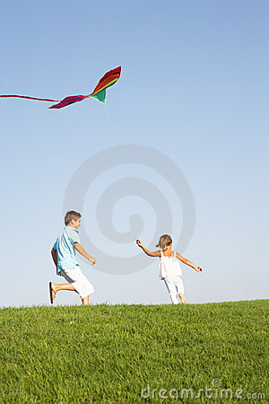 Young children run with kite