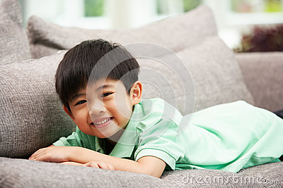Young Chinese Boy Relaxing On Sofa At Home