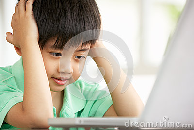 Young Chinese Boy Sitting Using Laptop At Home
