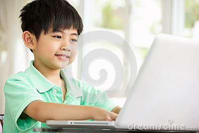 Young Chinese Boy Using Laptop At Home
