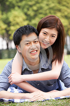 Young Chinese Couple Relaxing In Park Together