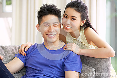 Young Chinese Couple Relaxing On Sofa At Home