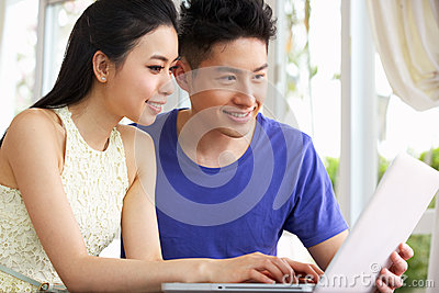 Young Chinese Couple Sitting Using Laptop At Home