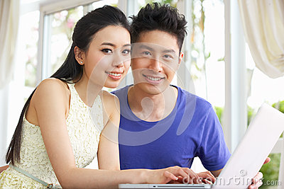 Young Chinese Couple And Using Laptop At Home