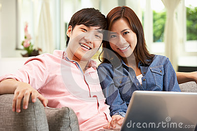 Young Chinese Couple Using Laptop Whilst Relaxing