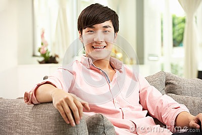 Young Chinese Man Relaxing On Sofa At Home