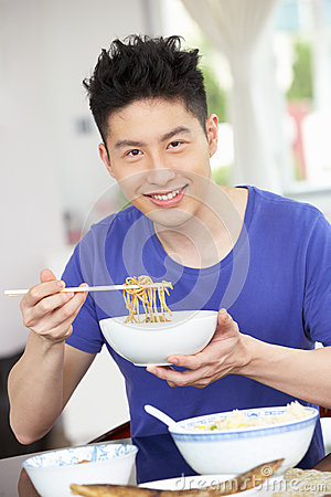 Young Chinese Man Sitting At Home Eating Meal