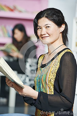 Young chinese student girl with book in library