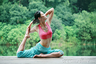 Young chinese woman practicing yoga outdoor