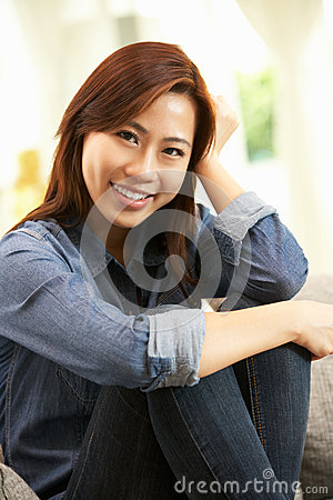 Young Chinese Woman Relaxing On Sofa At Home