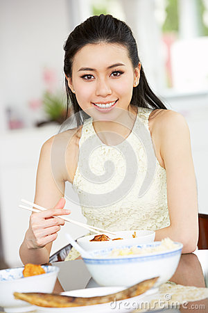 Young Chinese Woman Sitting At Home Eating Meal