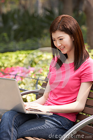 Young Chinese Woman Using Laptop Whilst  Relaxing