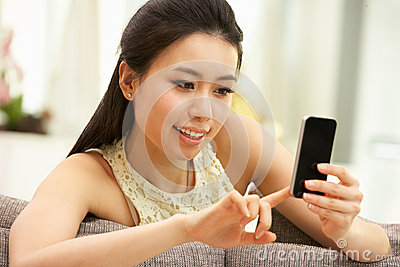 Young Chinese Woman Using Mobile Phone At Home