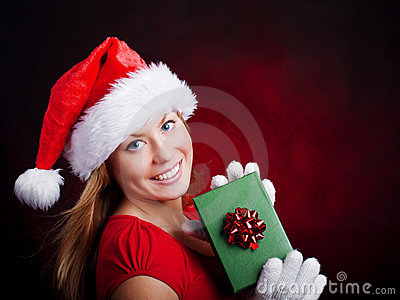 Young christmas woman holding present over dark