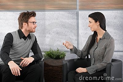 Young colleagues talking in office lobby